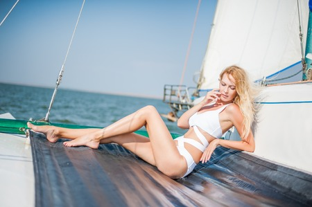 Young beautiful woman in fashion white swimsuit sitting on trimaran yacht in open sea or ocean