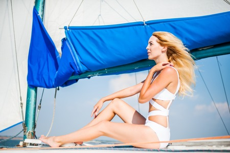 Portrait of beautiful young fashion woman sitting on sail boat or yacht in the sea wearing modern swimsuit