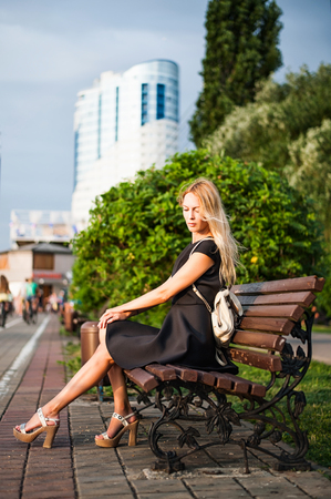 Beautiful woman in fashion black summer dress sitting on banch in modern city