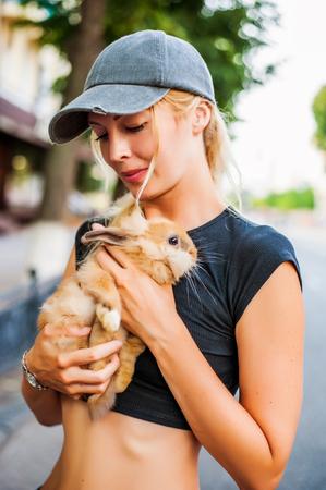 beautiful girl holding pet decorative rabbit outside