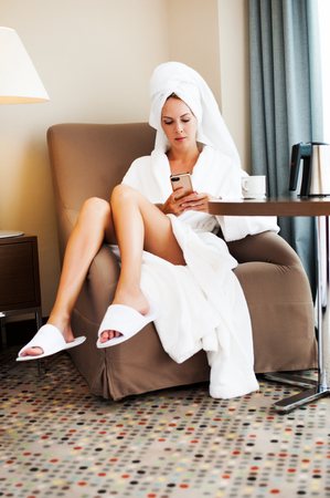 Morning beautiful girl after bathing with towel on head sitting in armchair and holding and writing phone in hands