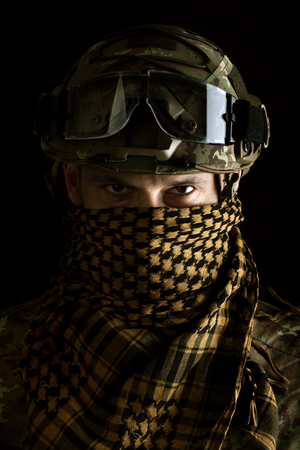 close up portrait of handsome military man. Macro shot on black background in special scarf on face