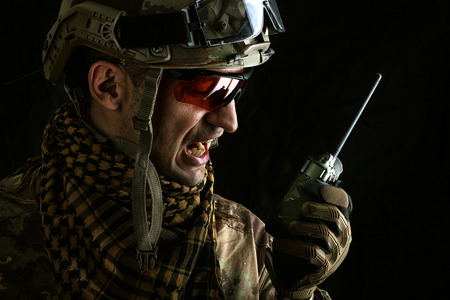 close up portrait of handsome military man. Macro shot on black background with portable radio transceiver