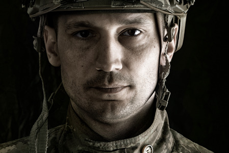close up portrait of handsome military man. Macro shot on black background looking at camera Stock Photo