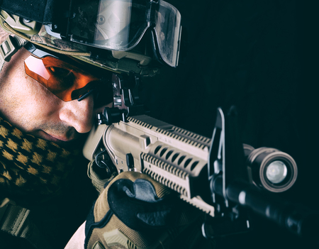 close up portrait of handsome military man. Macro shot on black background sniper with automatic rifle aiming and shooting Stock Photo