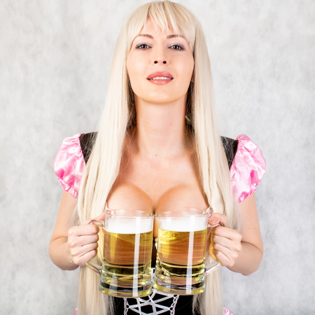Young beautiful blond oktoberfest woman with big neckline on female breast Holds two mugs with light beer