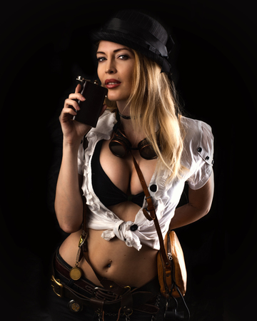 Sexy girl wearing steampunk costume on black background