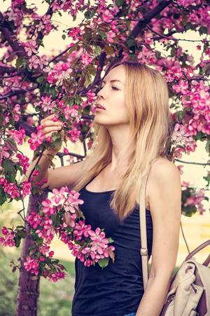 Young beautiful woman posing in Japan sakura garden. Macro view - Defocus floral background spring pink cherry flowers close up.