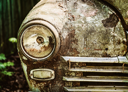 An old rusty abandoned car outdoors in the woods. broken car headlight close-up