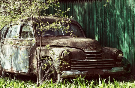 An old rusty abandoned car outdoors. broken car close-up view