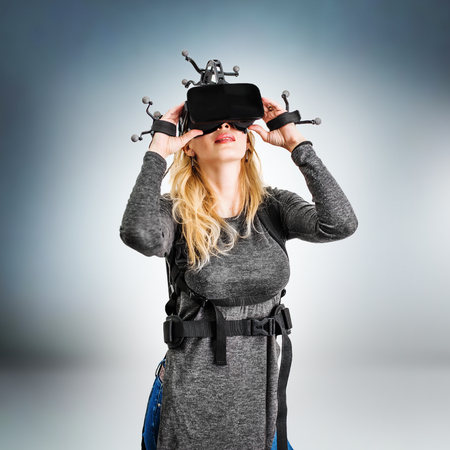 Virtual Reality vr shot. Young woman in studio on grey background