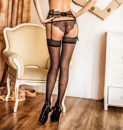 Beautiful long slender female legs in black stockings on high heels shoes