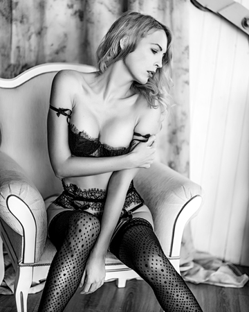 Beautiful young blond woman model in room in sexy lace lingerie. black and white