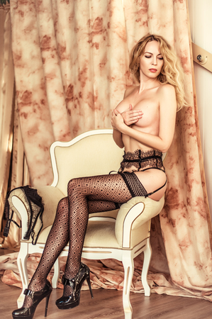 Beautiful young blond woman model in room in sexy lace lingerie
