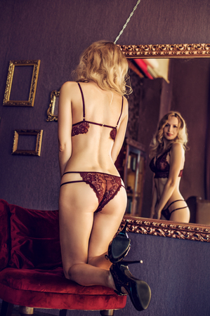 Beautiful young blond woman model in room in sexy lace lingerie stay back near mirror