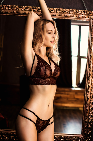Beautiful young blond woman model in room in sexy lace lingerie stay near mirror Stock Photo