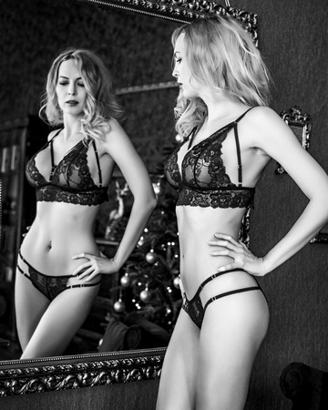 Beautiful young blond woman model in room in sexy lace lingerie stay near mirror. Black and white