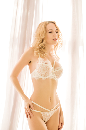 Beautiful young blond woman model in white room in sexy lace lingerie Stock Photo
