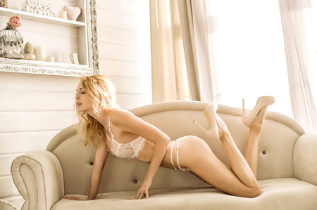 Beautiful young blond woman model in white room in sexy lace lingerie posing on coach