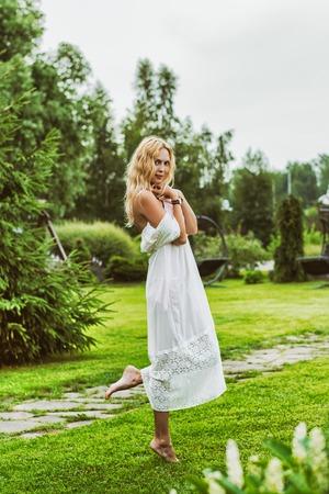 Beautiful young woman wearing long white dress Stock Photo