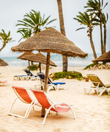 Focus on parasol. Sunbeds with umbrella made of straw on snow-white sand and palm trees on the beach near sea or ocean in Tunisia Stock Photo
