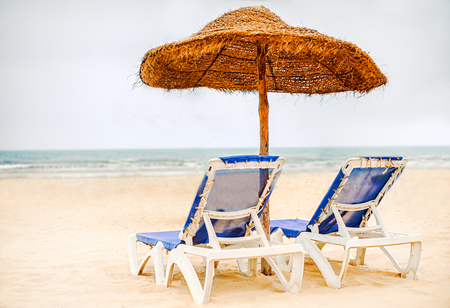 Focus on parasol. Sunbeds with umbrella made of straw on snow-white sand on the beach near sea or ocean in Tunisia