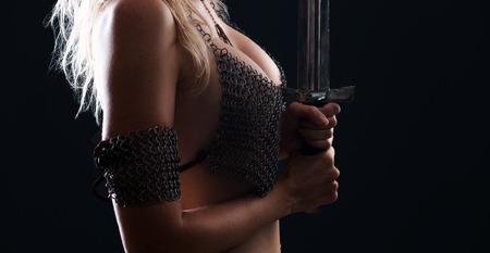 beautiful sexy warrior viking girl with a sword in hands on a black background
