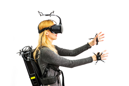 Beautiful woman touching air during VR experience isolated on white. She wearing Virtual reality glasses or goggles, processor in backpack on back and sensors for tracking on head and hands