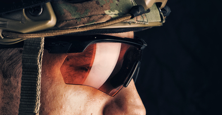 close up portrait of handsome military man in helmet and glasses. Macro shot on black background Stock Photo