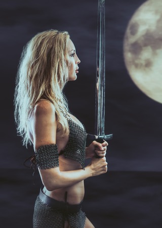 beautiful sexy warrior viking girl with a sword in hands. Midnight and moon