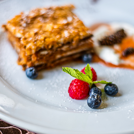 Layered honey cake on white plate with berries Stock fotó