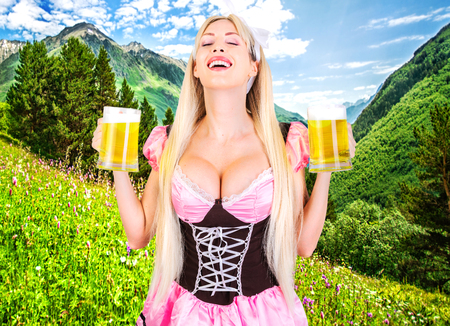 Young beautiful blond oktoberfest woman with big neckline on female breast Holds two mugs with light beer on meadow Banque d'images