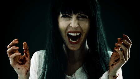Crazy bloody scary zombie woman screams at camera
