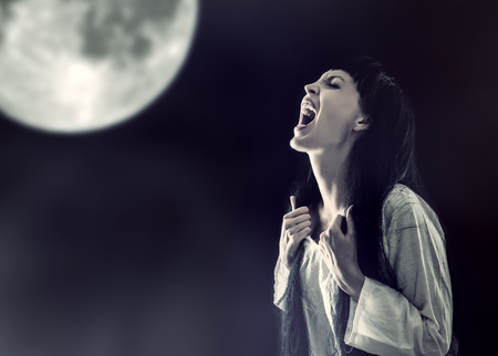 Halloween zombie woman screaming on full moon at night at midnight Banco de Imagens