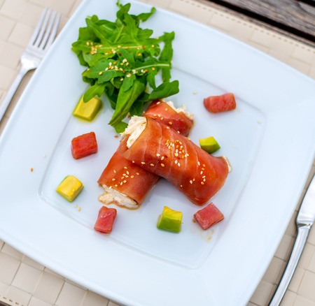 rolls of tuna with crab meat with slices of avocado and greens Stock Photo