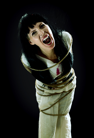 Halloween horror. Crazy bloody scary zombie vampire woman with fangs tied up with rope looks into the camera and screams on black background
