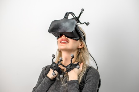 Beautiful woman on grey background. She wearing Virtual reality glasses or goggles on forehead, processor in backpack on back and sensors for tracking on head and hands 스톡 콘텐츠