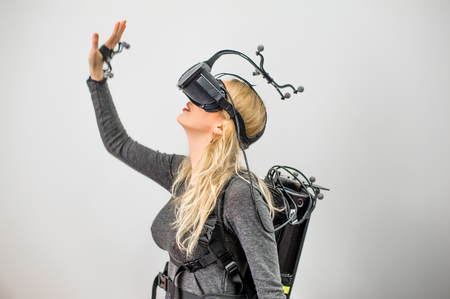 Beautiful woman on grey background. She wearing Virtual reality glasses or goggles on forehead, processor in backpack on back and sensors for tracking on head and hands Stock Photo