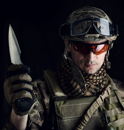 Dangerous military man in coumuflage preparing to attack with a sharp steel knife in his hand