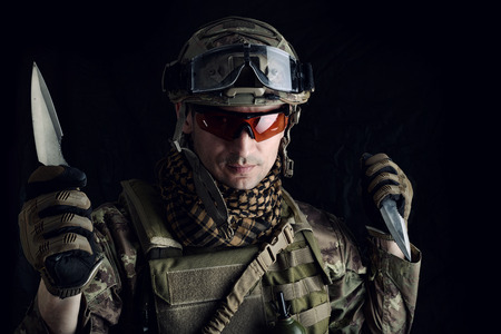 Dangerous military man in coumuflage preparing to attack with two sharp steel knife in his hand