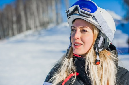 Young adult woman snowboarder or skier close up portrait wearing white healmet with mask in snow winter mountain Stock Photo