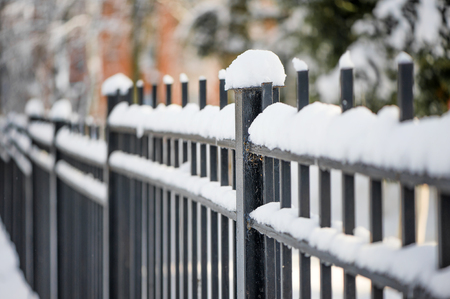 Defocus winter idea black metal fence in winter covered with snow Stock Photo
