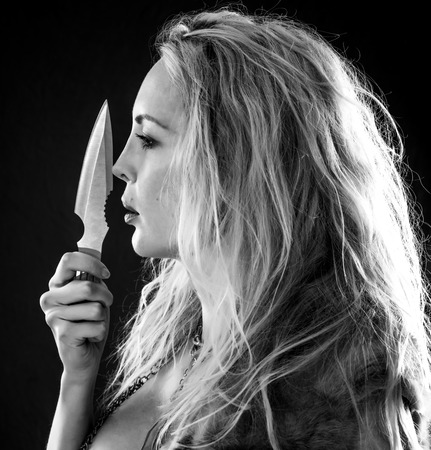 Throwing Knife in hand of beautiful woman. she is holding weapon near face in profile. Girl Viking or Amazon