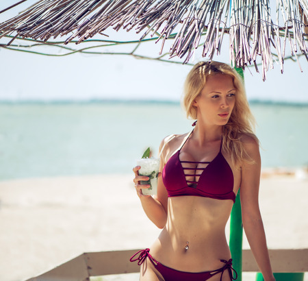 Beautiful young adult bikini woman on tropical resort with plastic glass of alcohol-free mojito cocktail