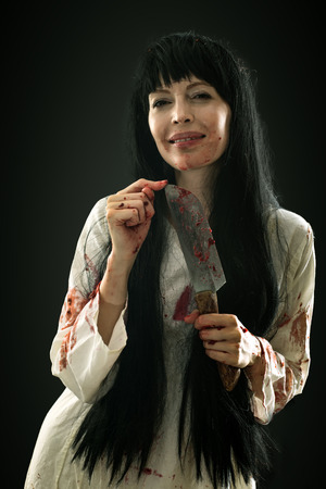 Halloween horror. Crazy bloody scary smiling maniac girl holding knife butcher cleaver looks into camera on black background