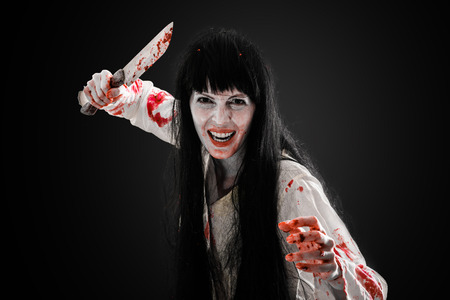 Halloween horror. Crazy bloody scary zombie girl holding knife butcher cleaver looks into camera on black background Stock Photo