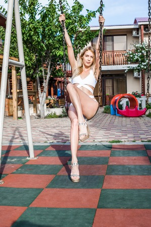 Beautiful young adult girl wearing white fashion swimsuit sitting metal swing outdoor
