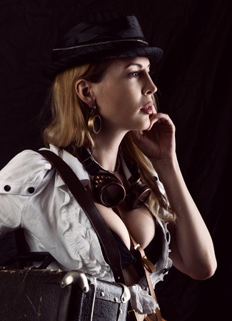 Sexy girl wearing steampunk costume with suitcase on black background