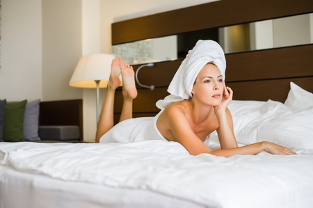 Young adult beautiful woman in hotel suit lies on a white bed. the towel is tied on the head