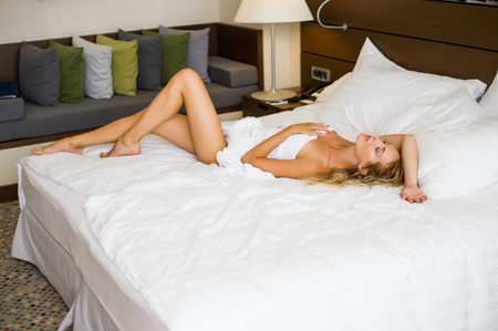Young adult beautiful woman in hotel suit in white bed in the morning